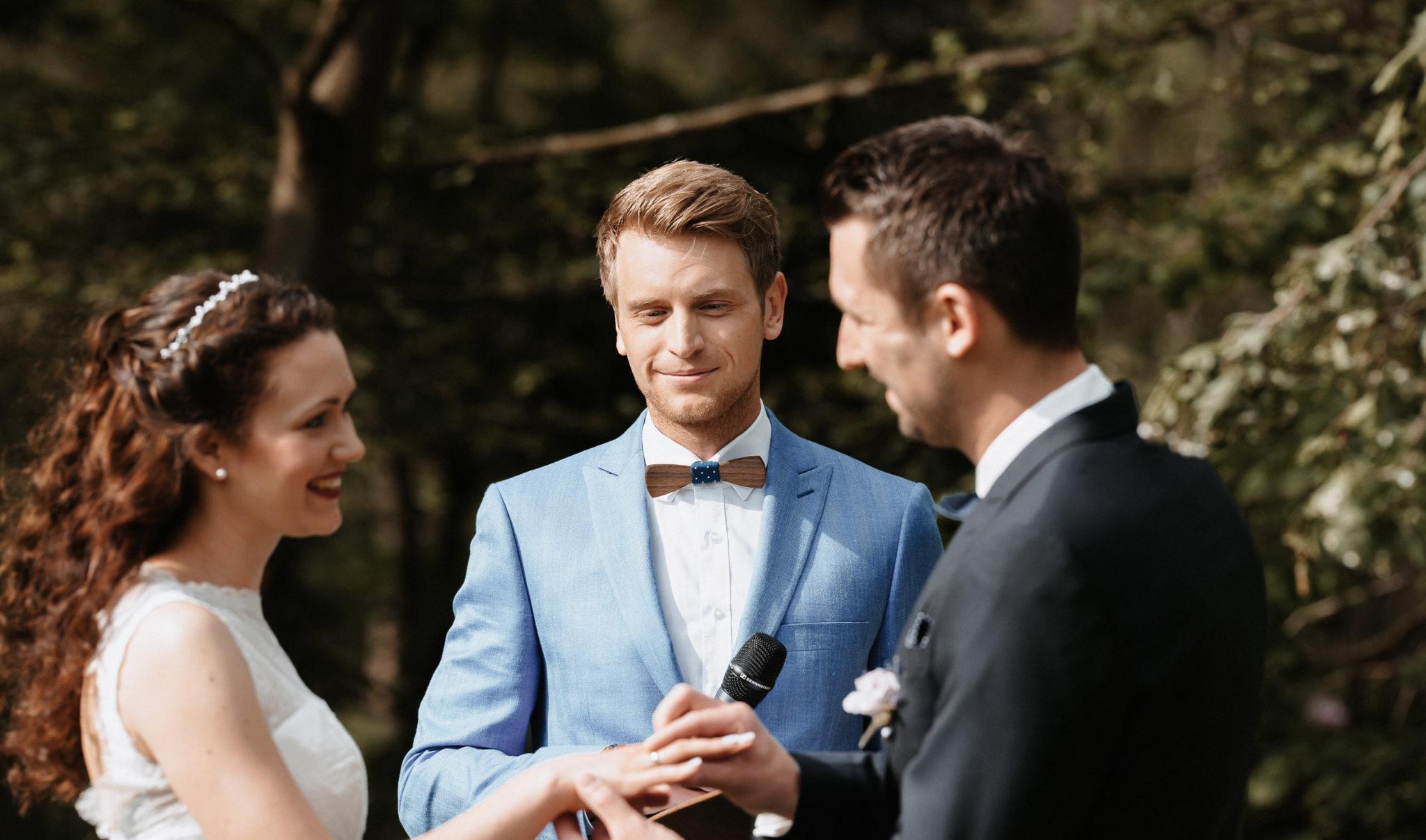 Freier Hochzeitsredner Julian Hügelmeyer mit Brautpaar während einer Freien Trauung beim Austausch der Ringe |Freier Redner werden